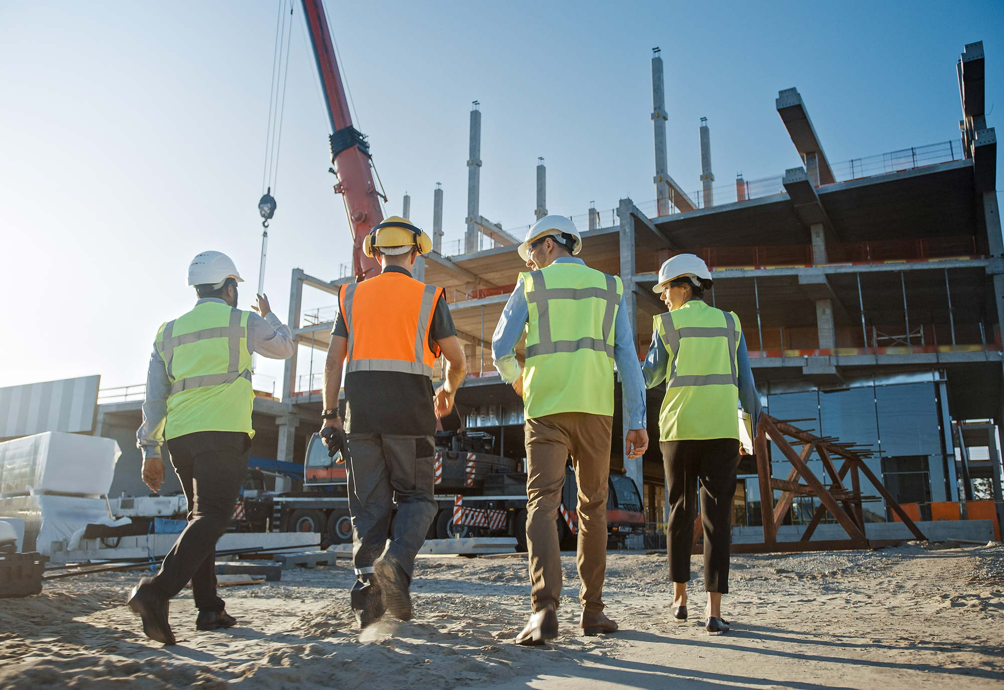 Three men and a women wearing high visability jackets and hard hats walk up to a construction site