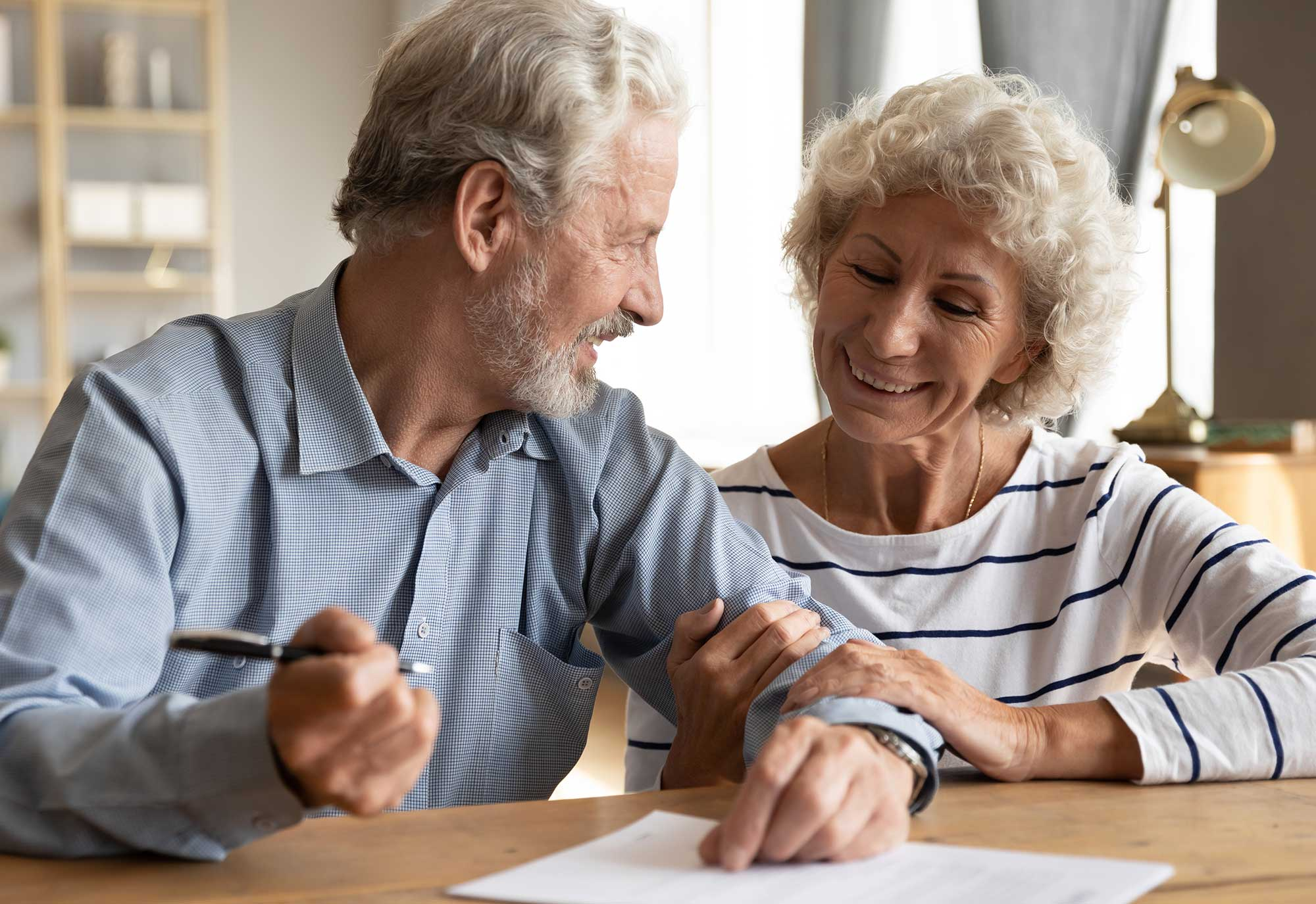 older couple sign forms at dining room table