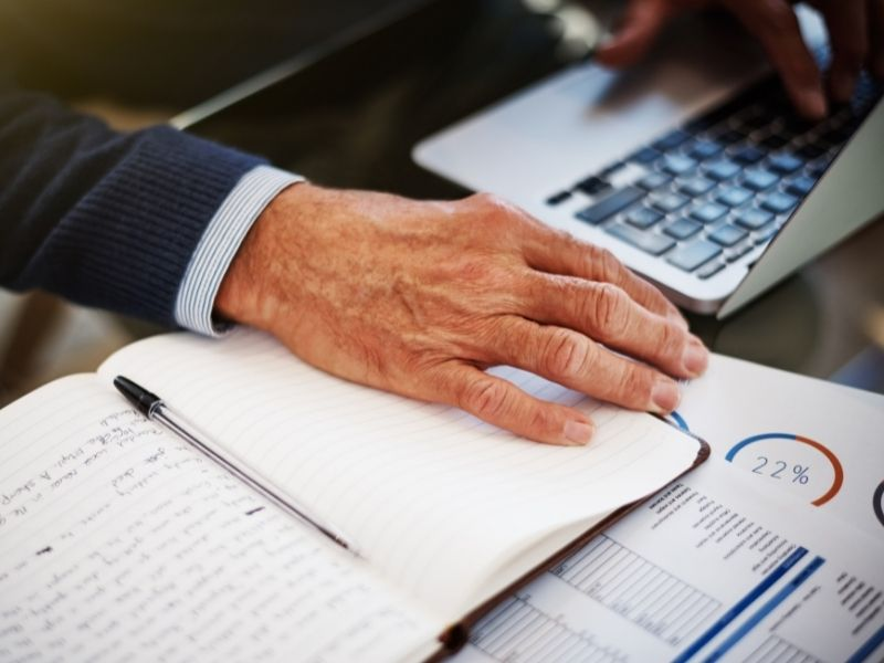 Businessman's hand on laptop and taking notes in a notebook