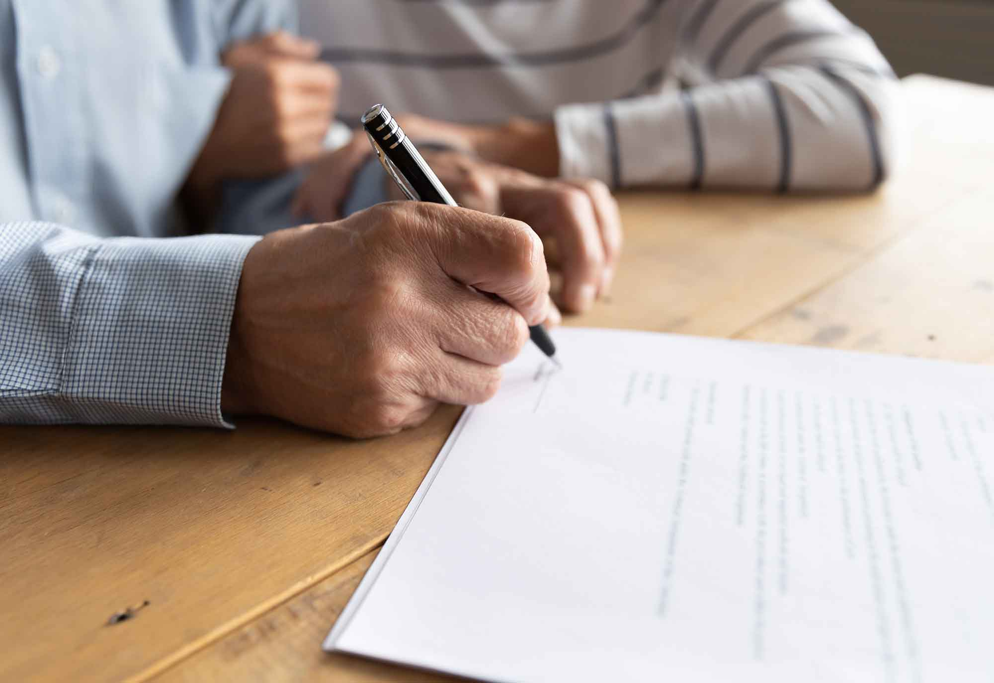 close up of older couple sitting at their dinning room table as the man holds a pen ready to sign a document