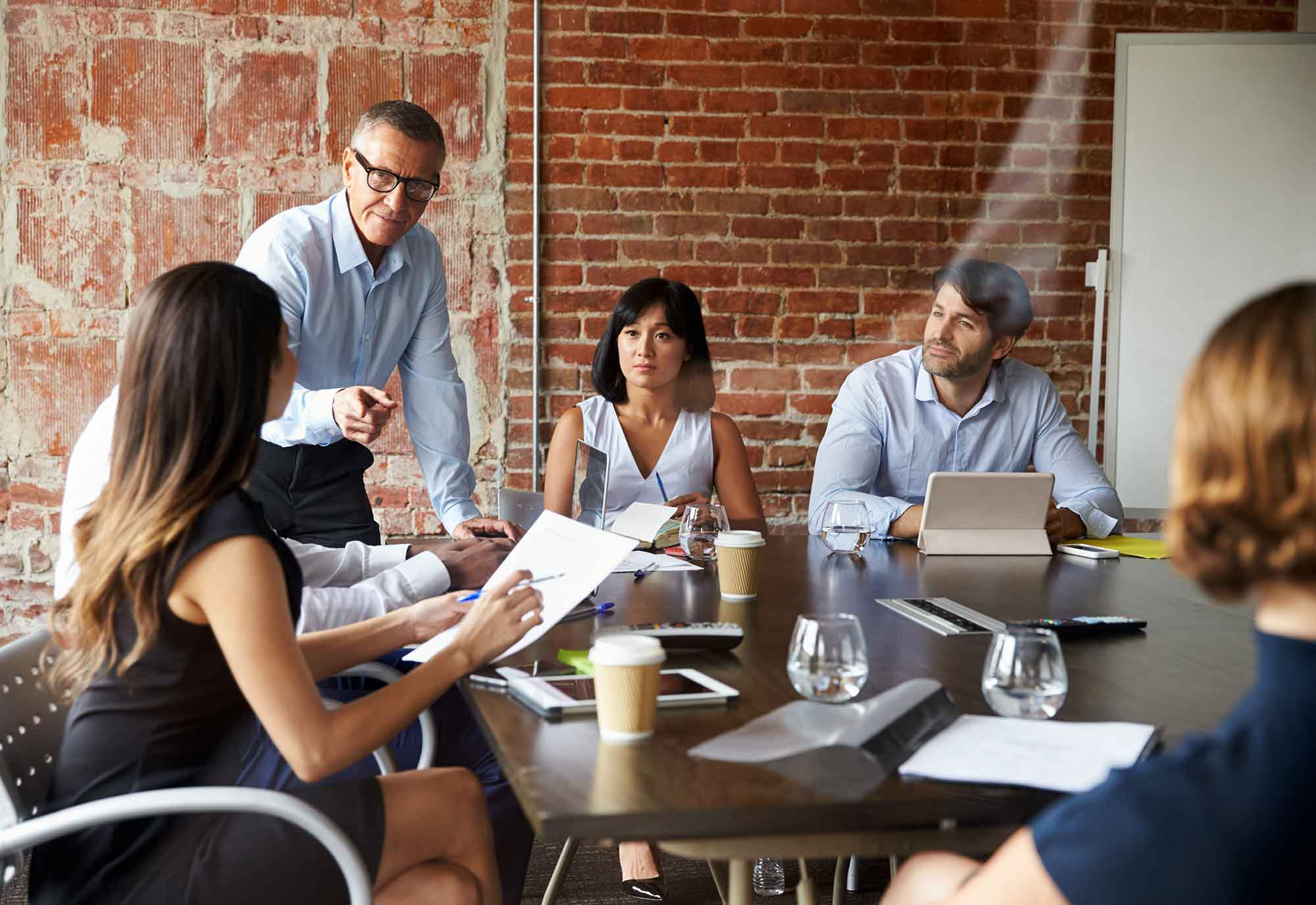 mixed group of male and female businesses workers communicate while sitting round a boardroom table in a modern office