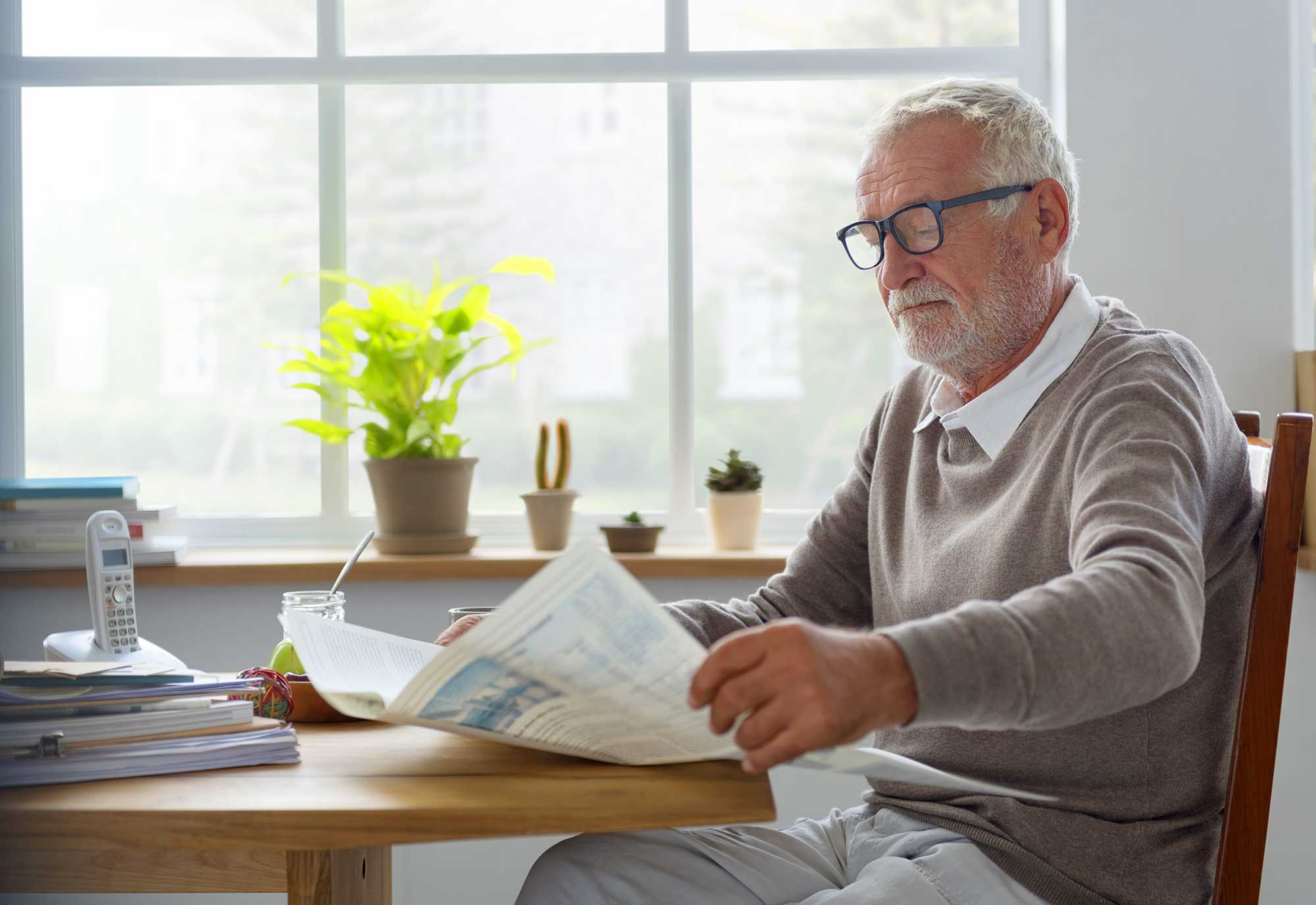Elderly man reading newspaper at a table