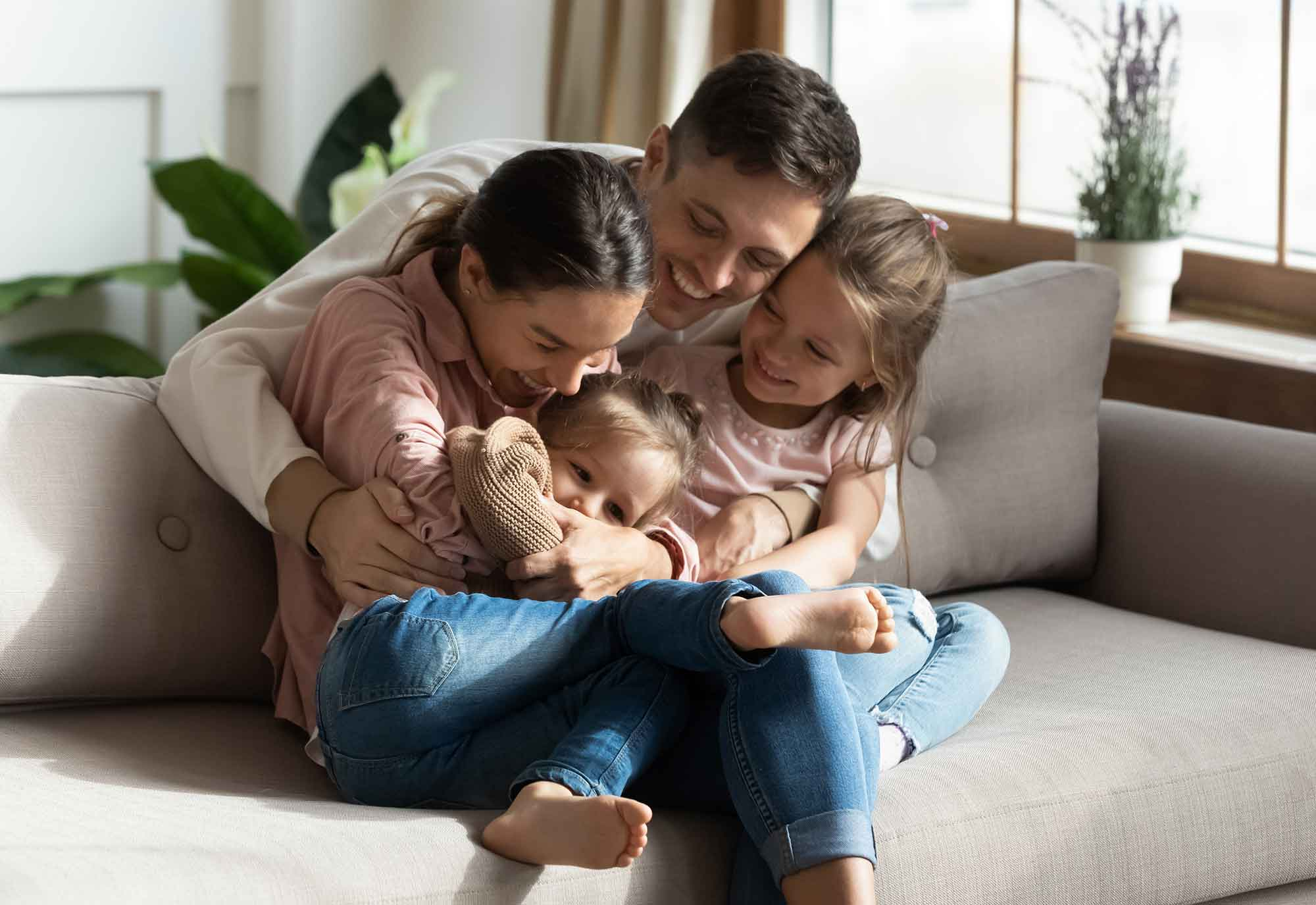 Man cuddles woman, child and baby as they sit and play on a sofa in their living room