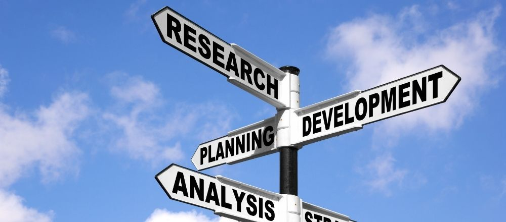 Signpost pointing the way to research and development and analysis and planning and strategy