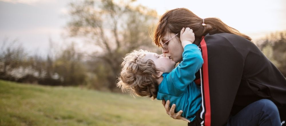 Mother and son playing in a field - mother is kissing son